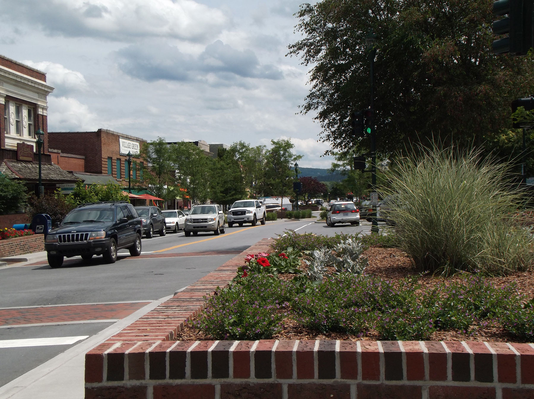 Cars traveling through a downtown Hendersonville street.