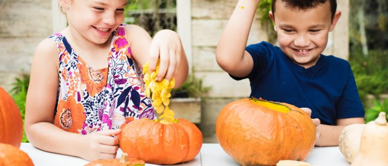 Two children carving out a pumpkin with their hands.