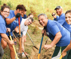 United Way volunteers holding shovels and wearing blue shirts.
