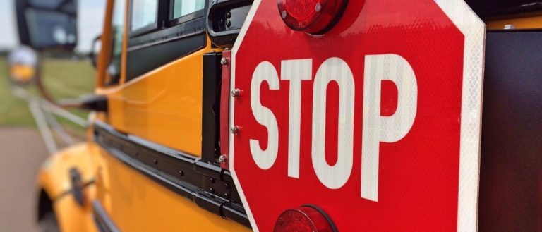 A red stop sign on a yellow school bus.