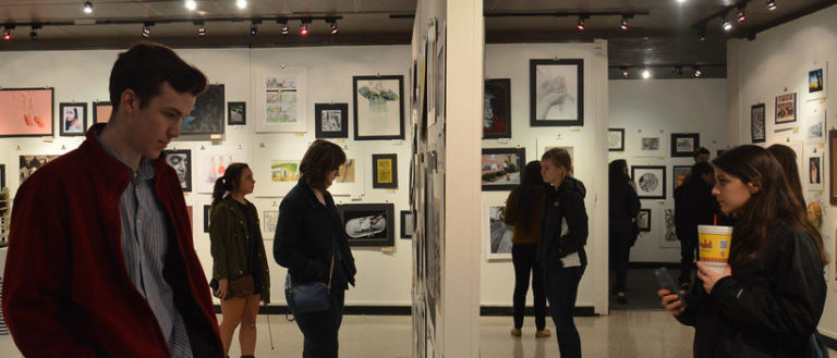 Individuals in an art gallery viewing various exhibits.