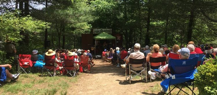 An audience facing the Carl Sandburg Folk Music Festival stage.