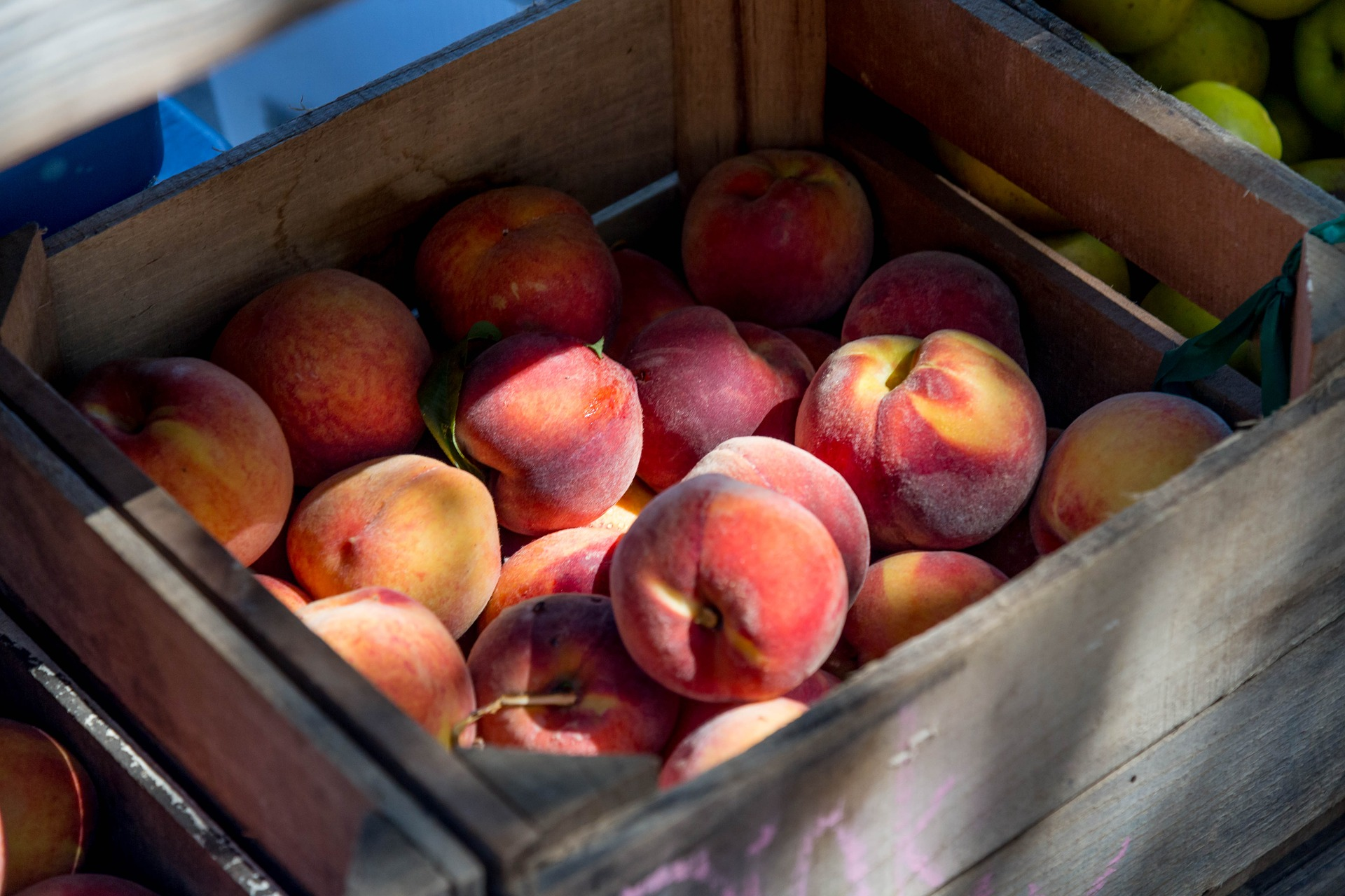 A shaded crate filled with peaches.