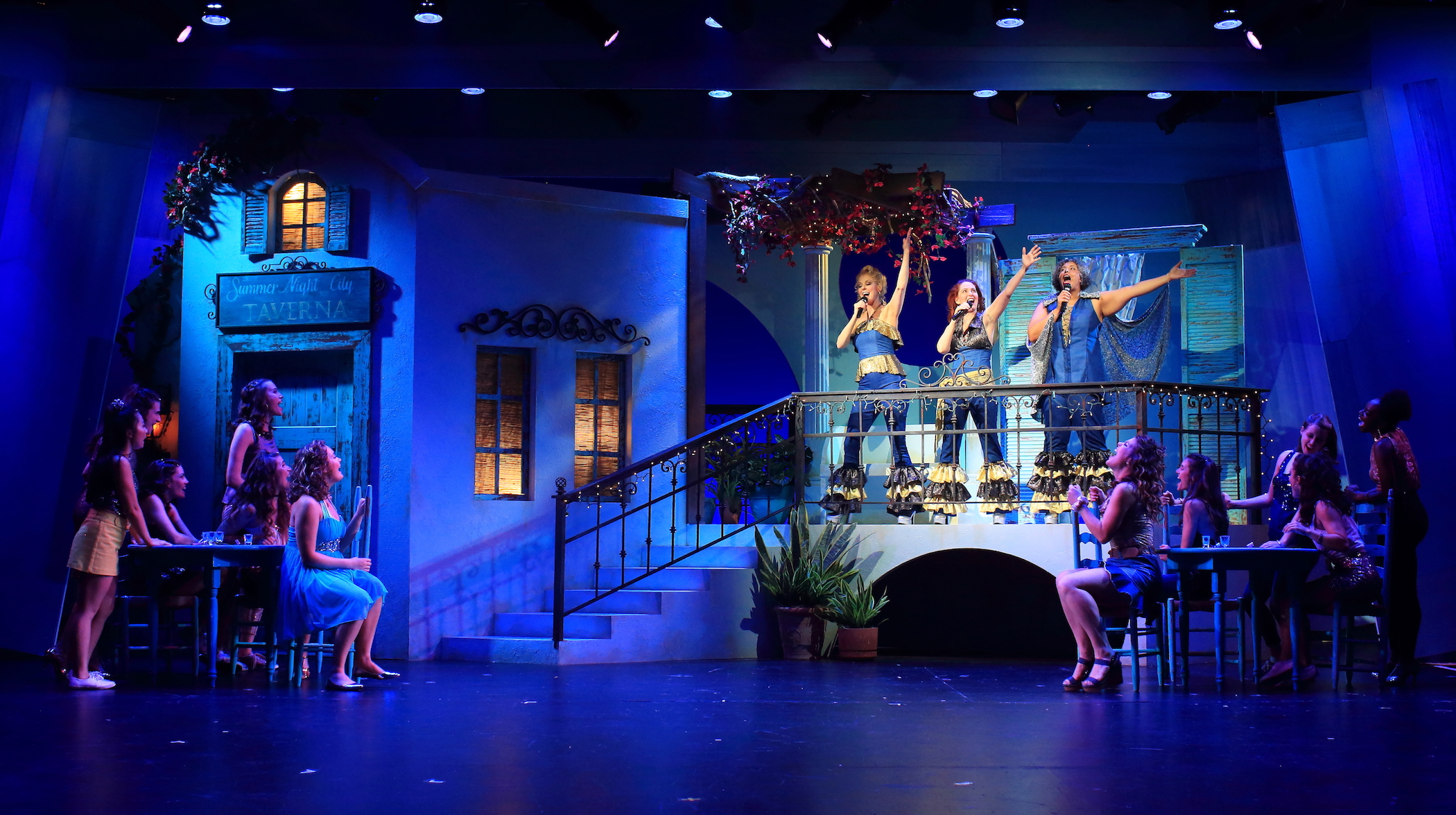 An blue-lit stage with actors during Mamma Mia at Flat Rock Playhouse.