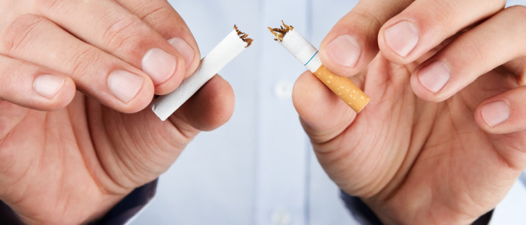 A person breaking a cigarette in half.