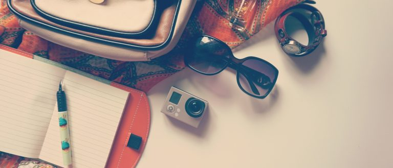 An assortment of common travel items on a white table.