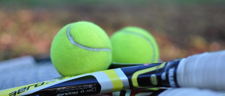 Tennis rackets on the ground with balls.