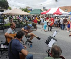 Musicians playing at a busy Henderson County Tailgate Market event.