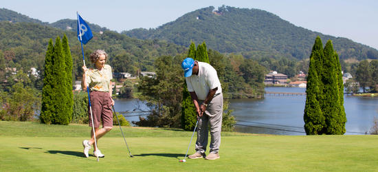Two people putting on a green at Lake Junaluska.