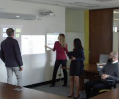 People interacting with an advanced wall projection during a presentation.