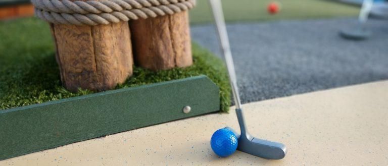 A putter and golf ball on a putt putt course.