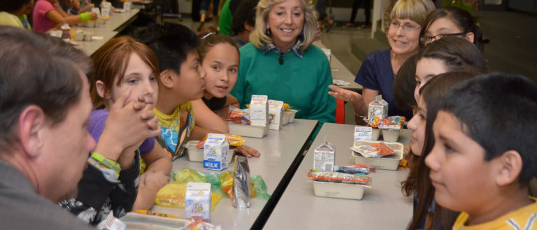 Adults eating a school lunch with children.