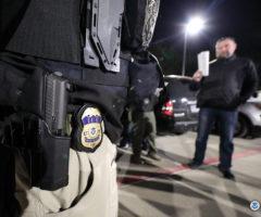 An ICE officer's waist holding a badge and gun near an immigration raid.